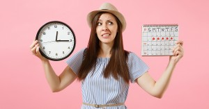 Shocked confused sad woman in blue dress holding round clock, periods calendar for checking menstruation days isolated on trending pink background. Medical gynecological concept; blog: 9 Reasons Your Period Is Late When You KNOW You're Not Pregnant