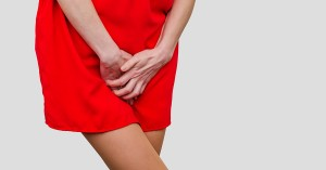 Woman in a red dress holding hands between legs. Experiencing pain, discomfort. Women's health, gynecology; blog: Yeast Infections: What's Normal, and When Should You Call Your OB/GYN?