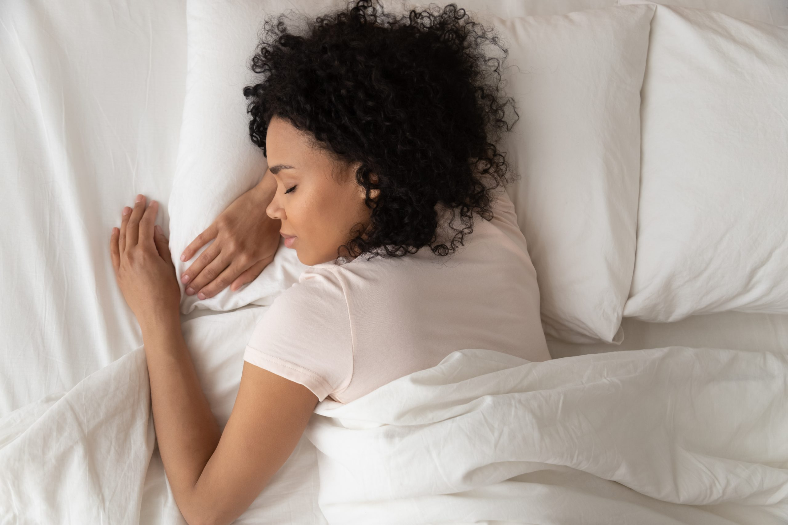 Healthy serene young african american girl sleeping well in comfortable cozy fresh bed on soft pillow white linen orthopedic mattress, calm sleepy black woman enjoy peaceful sleep at home, top view; blog: How Much Sleep Do You Need?