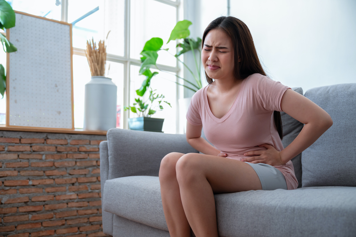 Asian young woman feeling abdominal pain while sitting on sofa couch in living room at home; blog: 10 Symptoms of Endometriosis