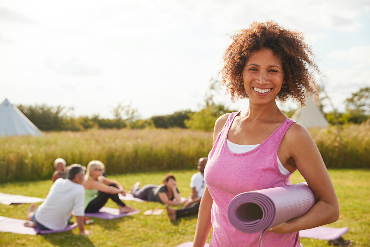 Portrait Of Mature Woman On Outdoor Yoga Retreat With Friends And Campsite In Background; blog: Women's Health Resolutions