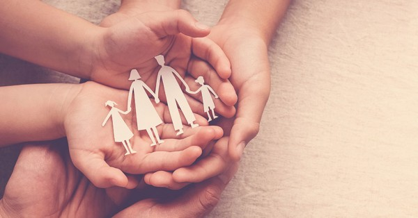 Adult and children hands holding paper family cutout, family home, foster care, homeless support concept; blog: What Are Family Planning Services?