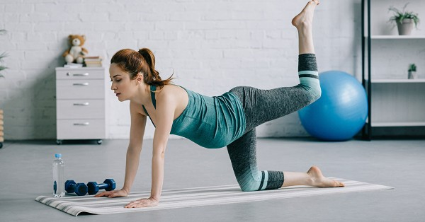 beautiful pregnant woman exercising on yoga mat in living room; blog: Your Guide to Exercising During Pregnancy