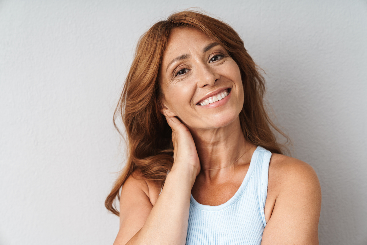 Portrait of an attractive smiling middle aged woman wearing casual outfit standing isolated over beige background, looking at camera; blog: What Is Perimenopause?